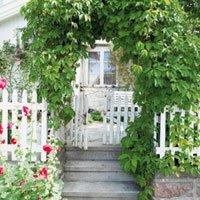 Gjerdet, porten og portalen avgrenser den private hagen fra allmennheten, men ønsker likevel hjertelig velkommen._