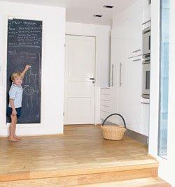Grovkjøkkenet er lagt et trinn opp fra hovedkjøkkenet. Det er brukt tavlemaling på kjøleskapssdøren, som brukes som familiens huskeliste over viktige gjøremål.