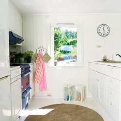 Kjøkkenkroken er liten, men rommet virker større og luftigere etter at alle flater ble malt lyse.