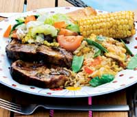 Grillet svinenakke, stekt ris, grillet mais og ananas er dandert med velsmakende saus.