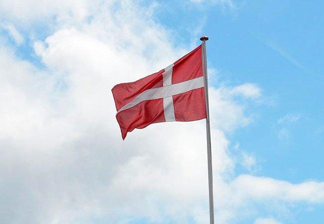 Det danske flag til top på hvid flagstang i træ.