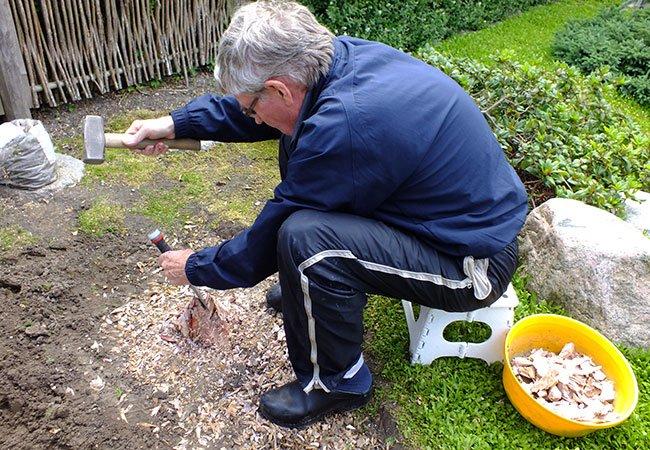 Mand fjerner træstub med hammer og mejsel