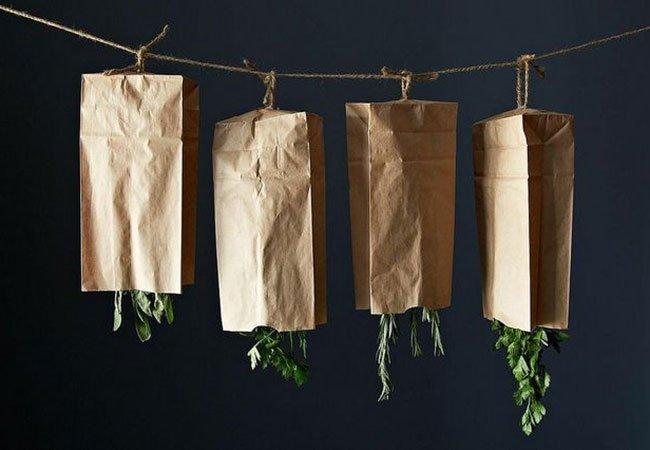 Krydderurter hænger til tørre under papirsposer.