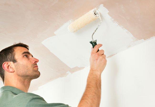 Malermester ruller loft over med hvid maling.
