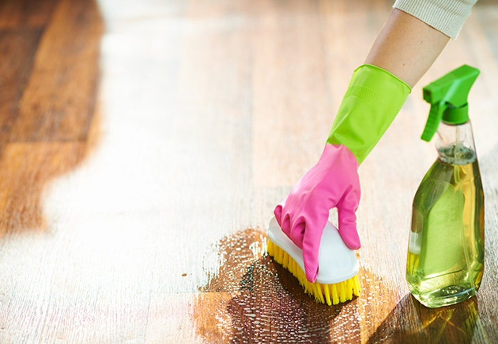 Woman With Cleaning Agent And Brush Wet Cleaning Floor