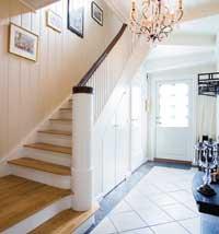 Hallen har fliser på gulvet og staselig trapp opp til andre etasjen.
