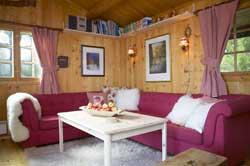 I den hyggelige stuen står solide stoler og trebord med rødmalt understell fra Lom Møbler. Stolsetene er nylig trukket om med koselig stoff fra Fabrikkutsalget Brumunddal.