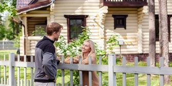 Mand og kvinde taler sammen over havehegn