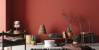 Stue malet i varm, rød farve med møbler, planter og pynt.
