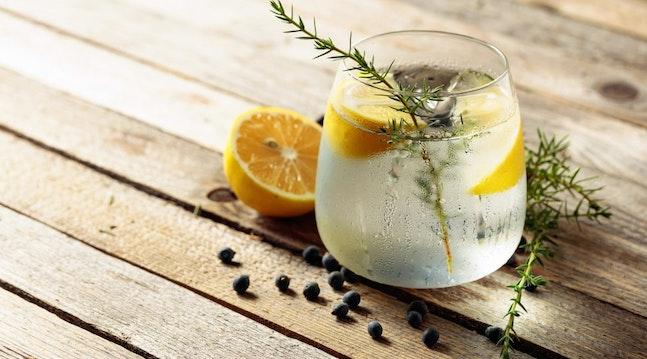 Gin og tonic med is, rosmarin, peberkorn og citrusfrugt.