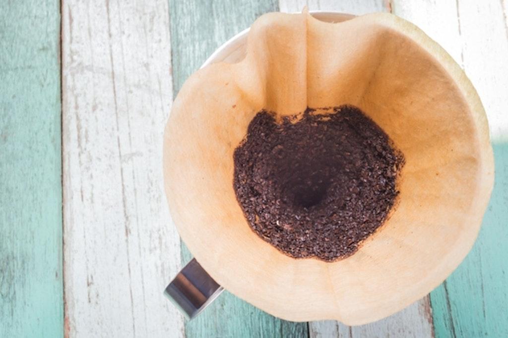Kaffegrums i kaffefilter på bord