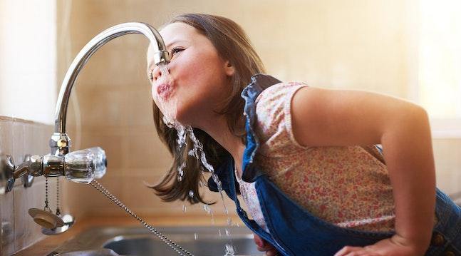 Pige drikker vand fra vandhane