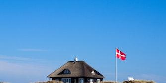 Sommerhus på en slette med et svejende Dannebrog og blå himmel.