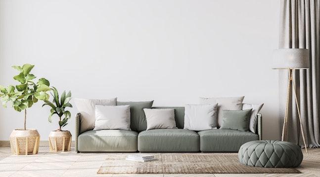 Lys stue med sofa, grønne planter, puf og lampe.
