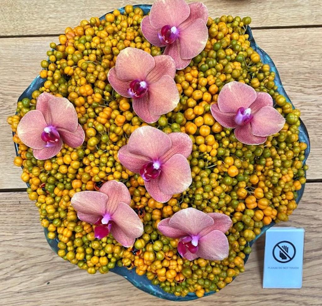 Blomsteropsats med små gule blomster og lyserøde orkideer