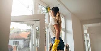 Dame står på stige og rengør sine vinduer.