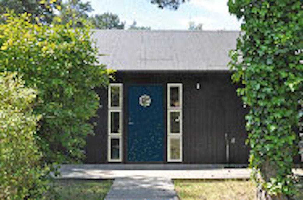 En blå dør mod en sort facade er et tidsløst valg