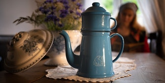 Madam Blå kaffekande står på bord. Ældre dame med gråt hår i baggrunden og en buket blomster i vase.