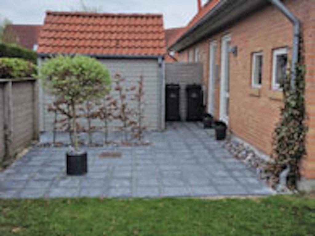 Der er lagt en flisegang på siden af huset så fliserne i for- og baghave er forbundet