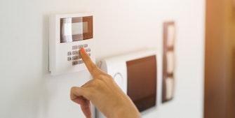 Kvinde i gang med at sætte sit alarmsystem til, så der ikke kommer indbrudstyve.